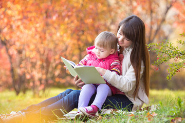 mother reading a book to kid outdoors in autumn