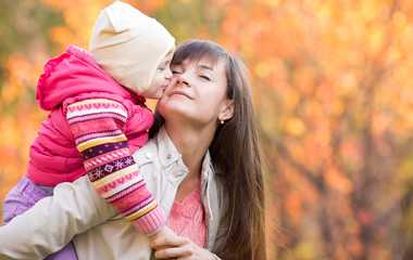 Beautiful woman with kid girl outdoors in fall. Child kissing mo
