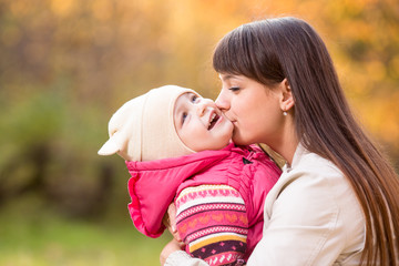 Young mother kissing kid girl outdoors in autumn park