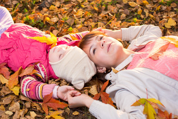 beautiful mother and kid laying on autumnal leaves outdoors