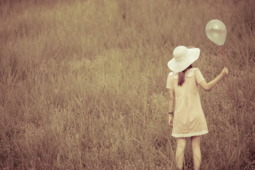 girl with balloons in a field