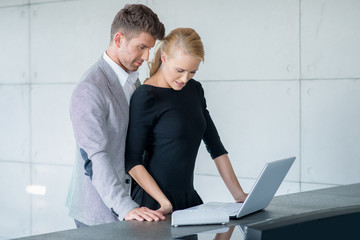 Middle Age Romantic Couple Testing Laptop on Table