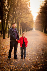father and son walking in the autumn park