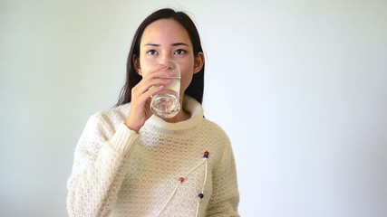 Asian girl drinking water isolated