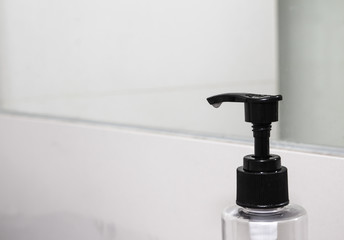 Liquid soap bottle on the sinks in modern bathroom