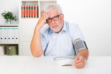 senior prüft seinen blutdruck