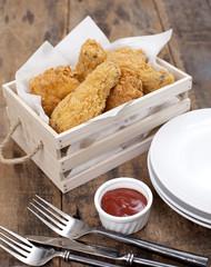 Fried Chicken in a basket on a wooden floor.