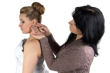 Bridesmade helping bride to wear earrings