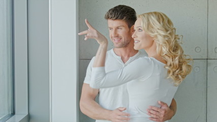 Attractive Young Couple In Front Of A Window