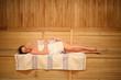 Beautiful young woman relaxing on a shelf in sauna