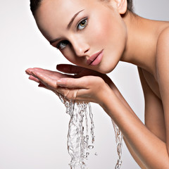 Caucasian woman washing face with water