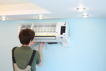 Young worker installs air conditioner in the room