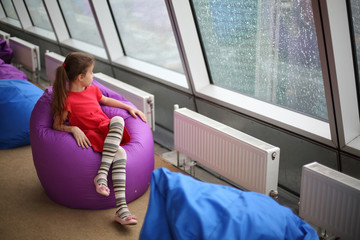 Little girl sitting on the ottoman and looking in large window