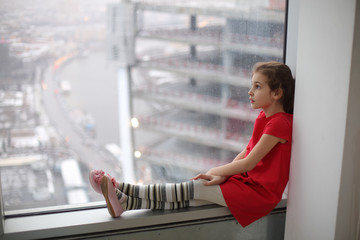 Little girl sitting on the windowsill of a large window