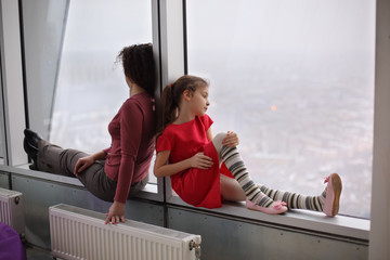 Woman and young girl sitting on the windowsill