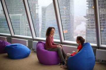 Woman talking with her daughter sitting on padded stools