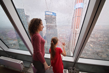 Mother and daughter looking through a large window