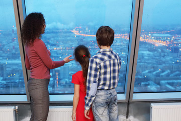 Mother shows children evening cityscape