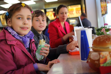 Mother with two kids have snack in fast food restaurant