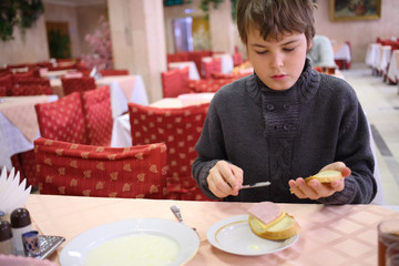Boy spreading butter on bread