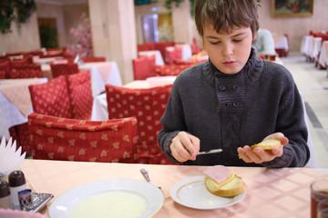 Boy spreading butter on bread