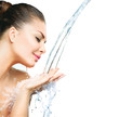Beautiful model girl with splashes of water in her hands