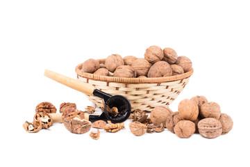 Walnuts on wicker basket and nutcracker.