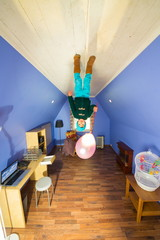 Little boy with air balloon standing on ceiling in room