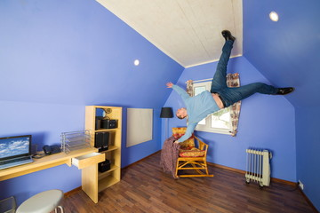 Man in jeans running on ceiling upside down at inverted house