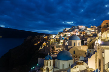 Churches of Oia village at dusk with dramatic sky, Santorini