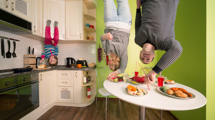 Family upside down in kitchen with table and dishes