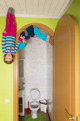 Two children upside down on ceiling at inverted house