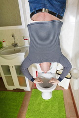 man is standing upside down on toilet bowl at inverted house