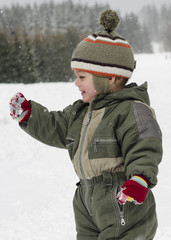 Happy child in winter playing in snow