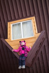Little girl sitting on the brown roof of upside-down house