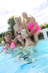 Happy 3-generation family enjoying swimming-pool