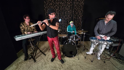 Musical band of four is working in studio with sand