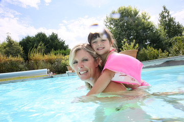 Mother and daughter playing in swimming-pool
