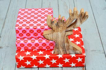 Gekleurde rode pakjes op oud hout met rendier