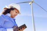 Female engineer working with a tablet at wind farm