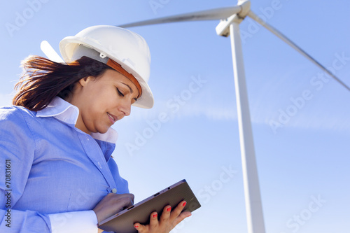 Female engineer working with a tablet at wind farm - 70831601