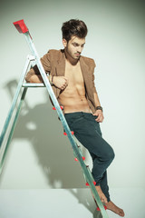Attractive fashion man leaning to a ladder