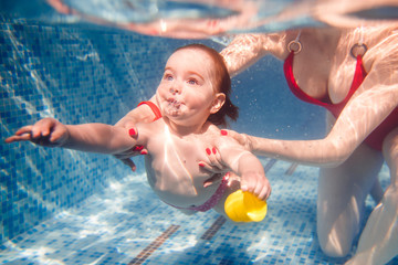 beautiful little girl swims underwater. child development
