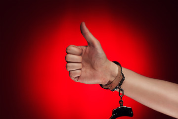 hand with thumb up and handcuffs opened concept