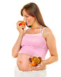 Pregnant woman eating fruit.