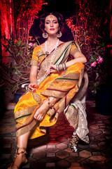 Indian beautiful girl sitting in in a yellow saree