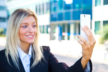 Beautiful business woman takes a selfie with her cell phone