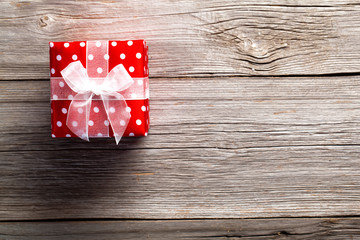 red gift box, polka dots, on wood background