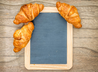 Fresh baked croissants on wooden table