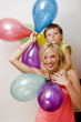 pretty family with color balloons on white background, blond